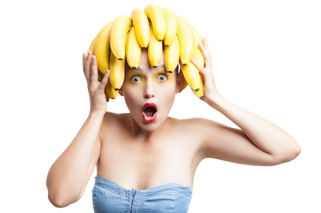 Удивленная модель с кучей бананов на голове, глядя в камеру. студия выстрел