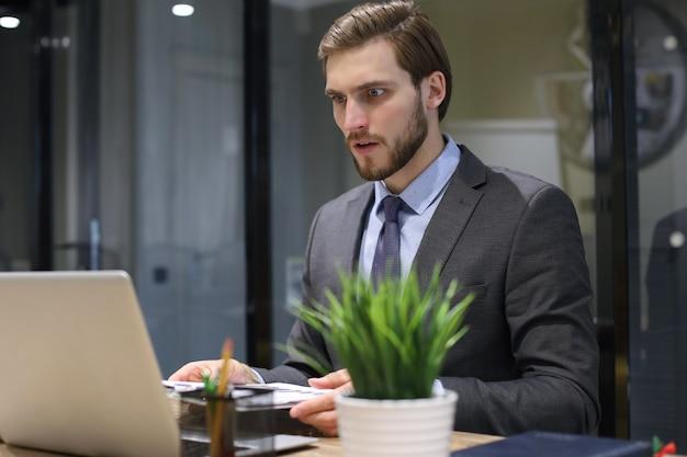 Удивлен современный деловой человек, работающий с ноутбуком, сидя в офисе.