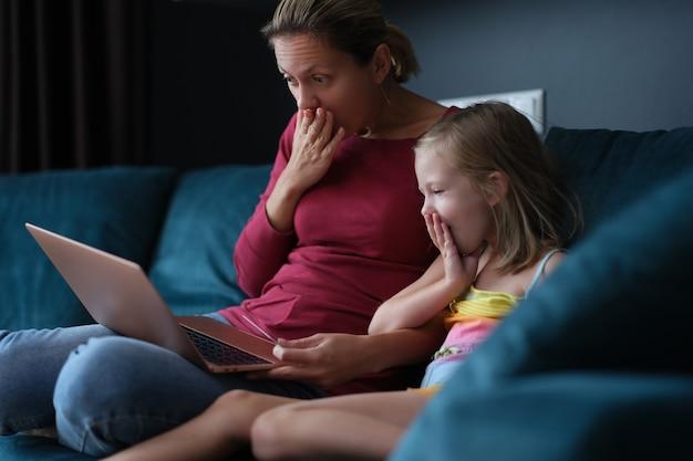 驚いたママと娘がソファに座ってノートパソコンの画面を見ています