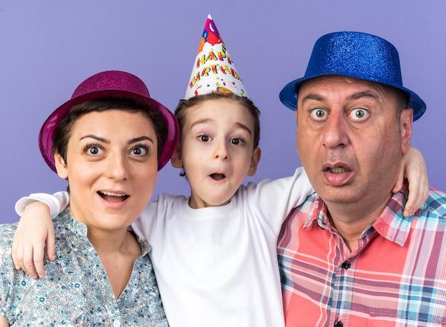 コピースペースで紫色の壁に隔離された息子と一緒に立っているパーティーハットで驚いた母と父