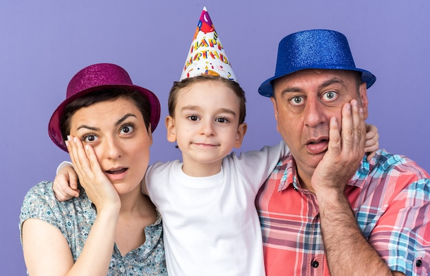 Surprised mother and father with party hats putting hands on face standing with their son isolated on purple wall with copy space