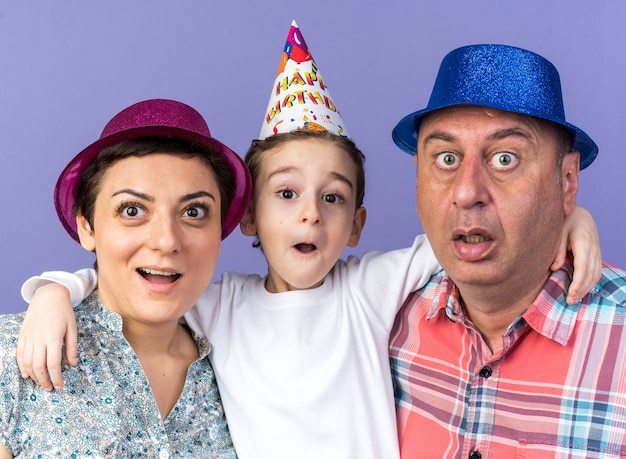 Surprised mother and father with party hats standing with their son isolated on purple wall with copy space