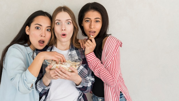 Surprised multiracial girlfriends with popcorn