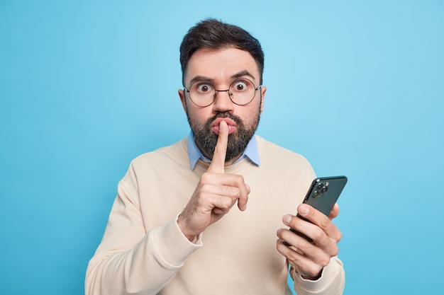 Surprised mysterious man makes silence gesture tells secret information uses mobile phone for online chatting and distance working wears spectacles casual sweater