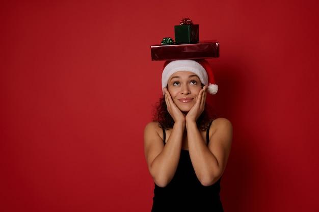 산타 모자를 쓰고 이브닝 블랙 드레스를 입은 신비한 여성이 머리에 있는 크리스마스 선물을 올려다보며 기뻐하고, 뺨에 손을 얹고, 행복을 표현하고, 빨간색 배경에 격리되어 있습니다.