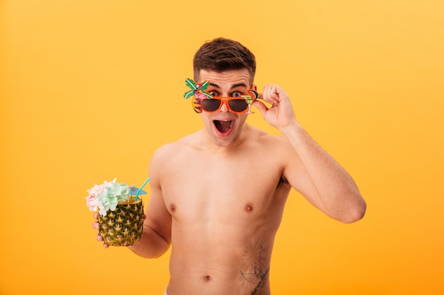 Surprised naked man in shorts and unusual sunglasses holding cocktail