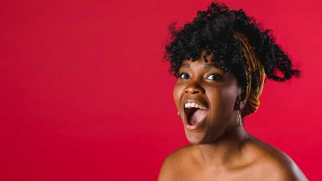 Surprised naked young black woman in studio with bright background