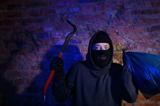 가방과 마스터 키로 벽돌 벽에 앉아 놀란 밤 갱스터