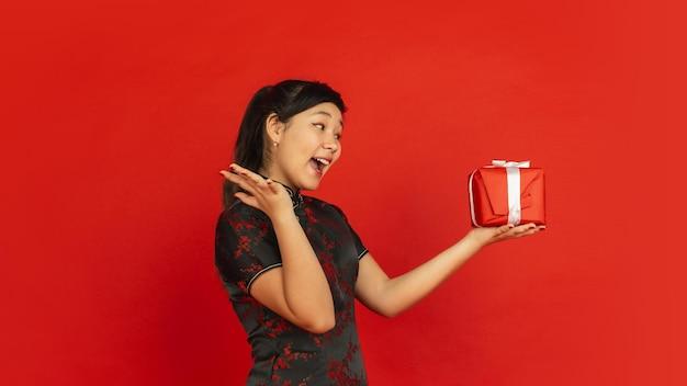 선물에 놀랐습니다. 해피 중국 설날. 빨간색 배경에 고립 된 아시아 젊은 여자의 초상화. 전통 옷을 입은 여성 모델이 행복해 보입니다. 축하, 휴일, 감정. copyspace.