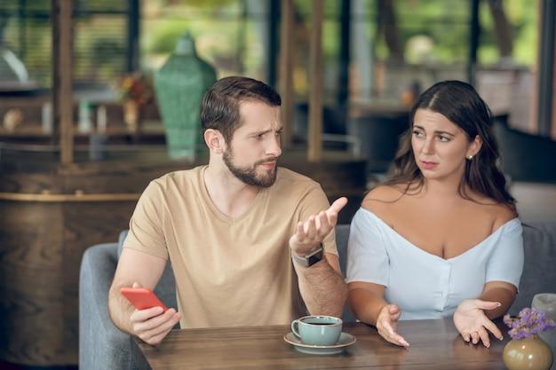 놀란 불쾌한 여자가 카페에서 오후에 앉아 몸짓으로 스마트 폰으로 요청하고 부주의 한 남자