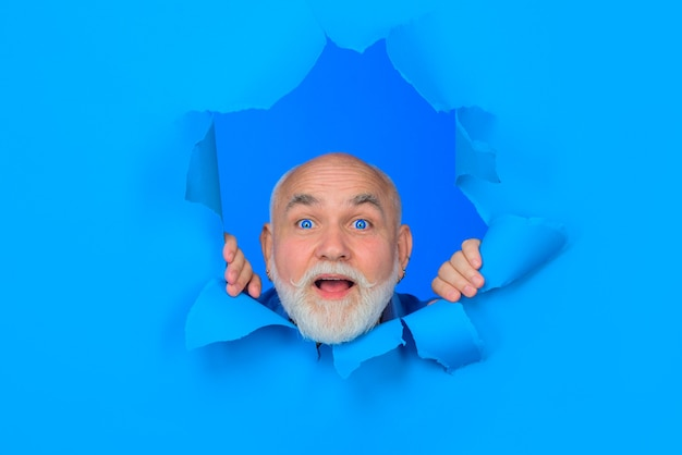 Surprised old bearded man through hole in blue paper copy space for advertising discount sale season