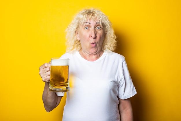 맥주 한 잔과 흰색 티셔츠에 놀란 된 늙은 금발의 여자