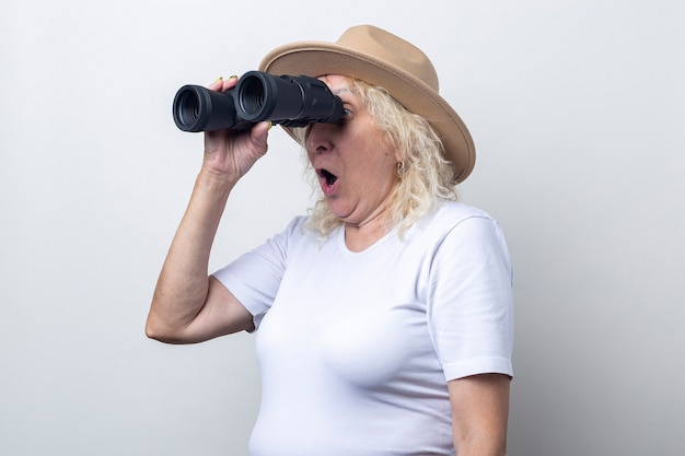 Surprised old woman holding binoculars on a light background.