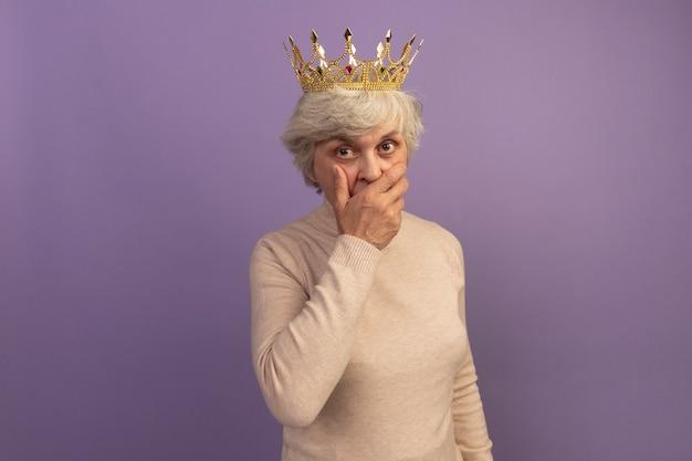 Donna anziana sorpresa che indossa un maglione dolcevita cremoso e una corona che tiene la mano sulla bocca isolata sul muro viola con spazio per le copie