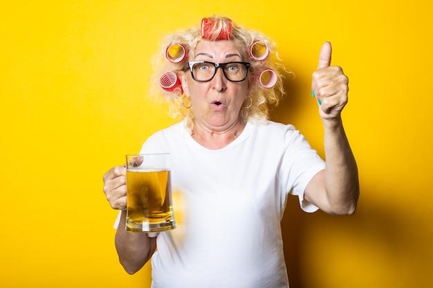 노란색 표면에 손 제스처를 엄지 손가락을 보여주는 맥주 한 잔과 머리카락 curlers와 놀란 늙은 여자