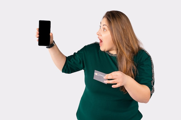 Surprised overweight woman looking to mock up blank smartphone screen to internet payment app large woman holding credit bank card