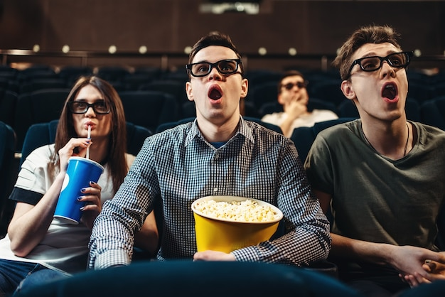 Surprised people in 3d glasses with popcorn and drinks watching movie in cinema. entertainment business