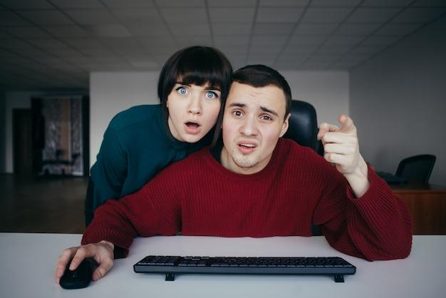 Удивленные люди эмоционально офисные работники воспринимали это тем, что видели на экране компьютера на фоне офиса