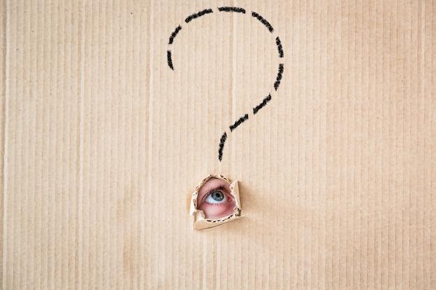 Удивленный человек, глядя через дырку из картона. скопируйте место для вашего текста