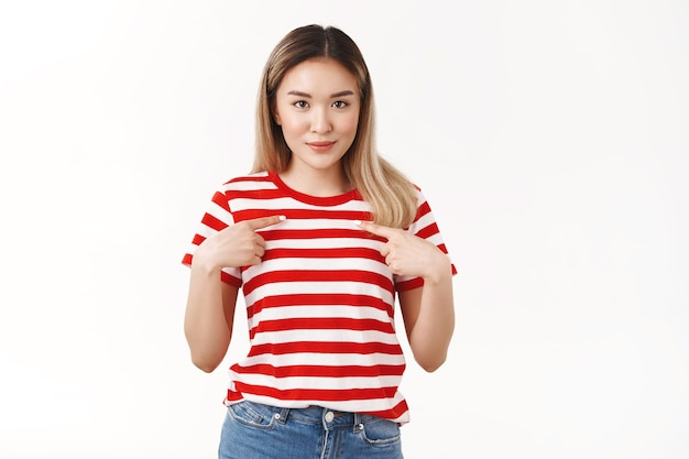 Surprised pleased silly cute asian blond girl pointing herself index fingers pressed chest look camera awaiting result amazed glance asking question is it for me, was chosen picked white wall