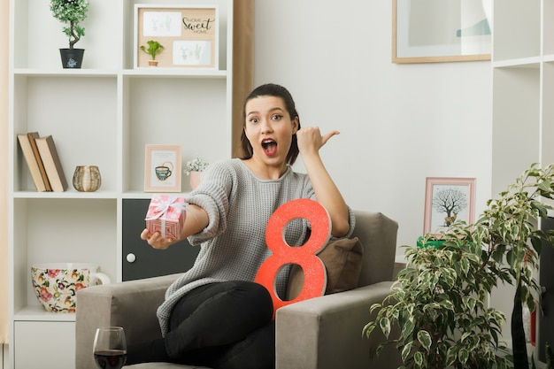 Punti sorpresi a lato bella ragazza nel giorno delle donne felici che regge il presente alla telecamera seduta sulla poltrona in soggiorno