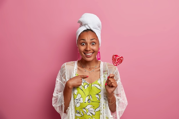 Surprised positive dark skinned woman looks with questioned expression smiles broadly holds sweet tasty candy dressed in casual domestic clothes isolated over pink wall. do you mean me