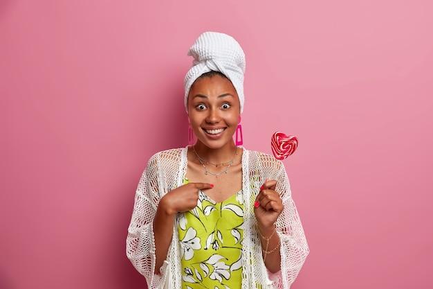驚いたポジティブな黒い肌の女性は、疑わしい表情の笑顔で、ピンクの壁の上にカジュアルな家庭服を着た甘いおいしいキャンディーを広く持っています。私のことですか