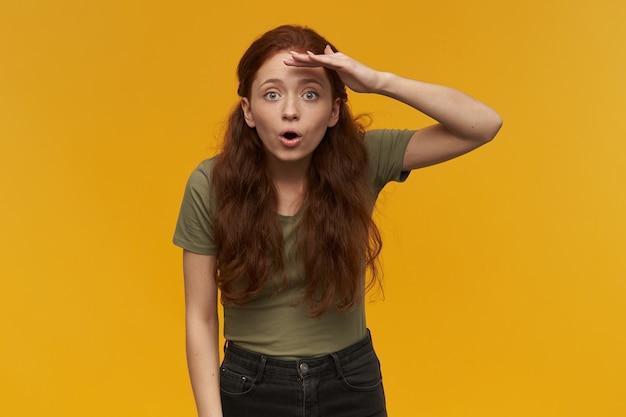 긴 생강 머리를 가진 놀랍고 긍정적 인 여성. 녹색 티셔츠를 입고. 사람과 감정 개념. 손바닥으로 눈을 가리고 먼 거리를 응시합니다. 오렌지 벽 위에 절연