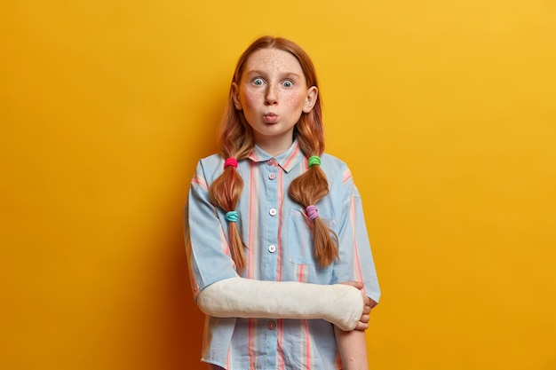 Surprised preteen girl pouts lips and looks with bugged eyes, makes funny grimace and foolishes around, wears gypsum on broken arm after accident on road. children, face expressions