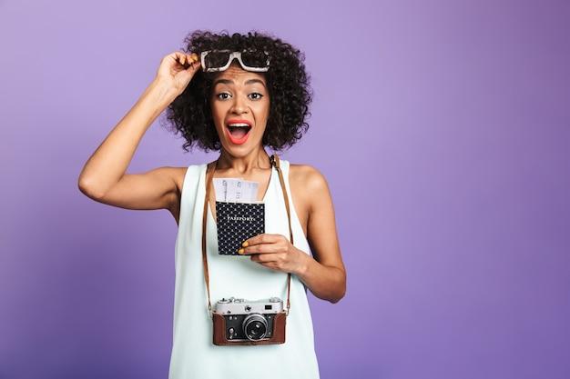 Удивленная симпатичная африканская женщина снимает солнцезащитные очки и смотрит прямо во время подготовки к поездке на фиолетовом фоне