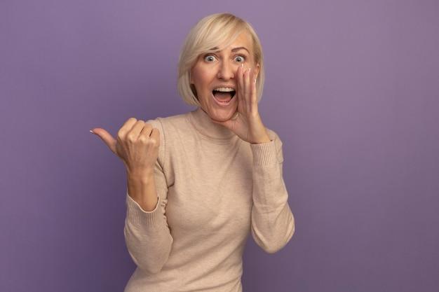 驚いたきれいな金髪のスラブの女性は、紫色の壁に隔離された側を指している口の近くに手を握ります