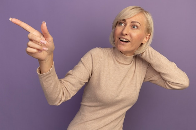 놀란 예쁜 금발의 슬라브 여자는 보라색에 측면을보고 가리키는 머리에 손을 넣습니다.