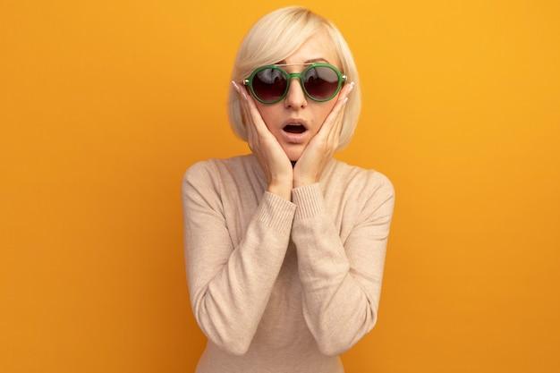 La donna slava abbastanza bionda sorpresa in occhiali da sole mette le mani sul viso isolato sulla parete arancione