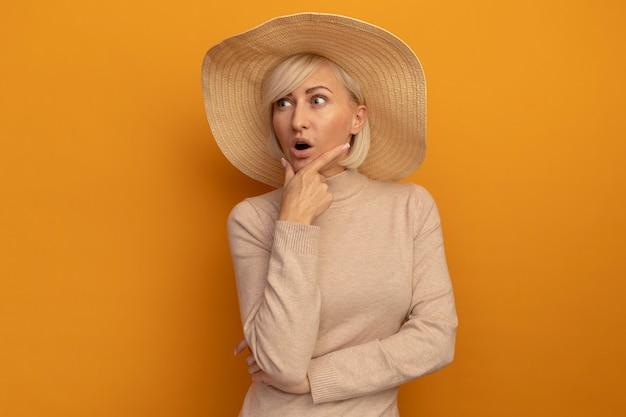 ビーチ帽子をかぶった驚いたきれいな金髪のスラブ女性は、オレンジ色の側面を見ているあごを保持します