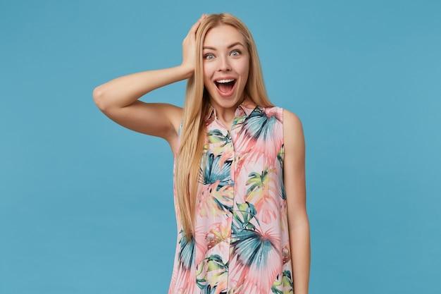 긴 머리가 꽃 무늬가있는 낭만적 인 드레스에 포즈를 취하는 놀란 예쁜 금발의 여자, 넓은 눈을 뜨고 넓게 웃으면 서 그녀의 머리에 행복하게 손을 올리십시오.