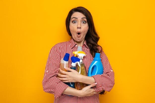 Sorpresa, bella donna caucasica delle pulizie che tiene in mano spray e liquidi per la pulizia