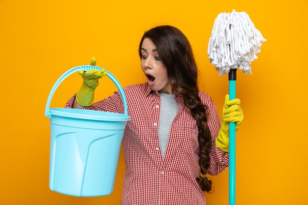 Surprised pretty caucasian cleaner woman with rubber gloves holding mop and looking at bucket