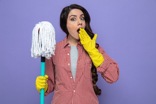 Surprised pretty caucasian cleaner woman with rubber gloves holding mop and putting hand on her mouth