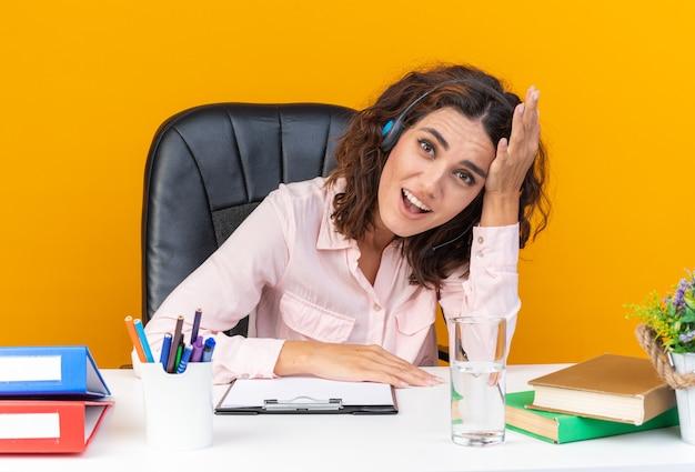 Operatore di call center femminile piuttosto caucasico sorpreso sulle cuffie seduto alla scrivania con strumenti da ufficio mettendo la mano sulla fronte guardando davanti