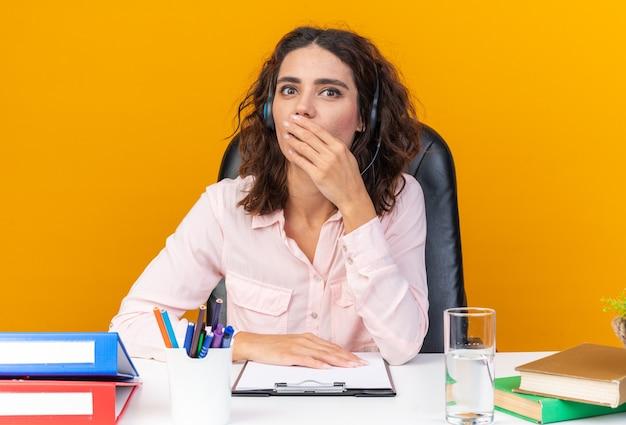 Operatore di call center femminile piuttosto caucasico sorpreso sulle cuffie seduto alla scrivania con strumenti da ufficio che le mettono la mano sulla bocca