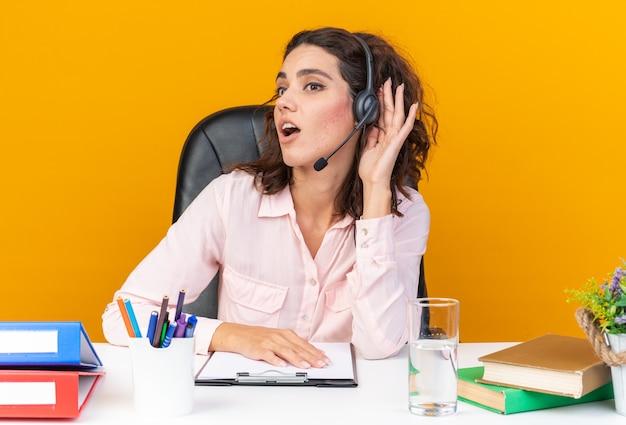 Удивленная симпатичная кавказская женщина-оператор колл-центра в наушниках сидит за столом с офисными инструментами, держа руку рядом с ухом, пытаясь услышать и глядя в сторону