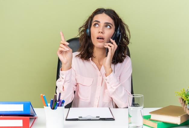 緑の壁に隔離された電話で話しているオフィスツールと机に座っているヘッドフォンで驚いたかなり白人の女性のコールセンターのオペレーター