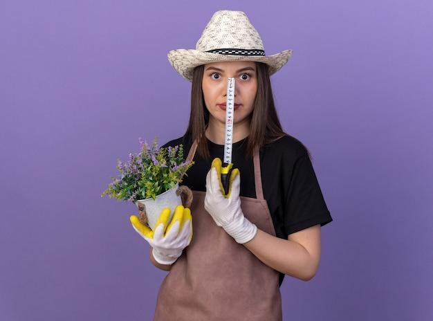 Sorpreso giardiniere femmina caucasica che indossa cappello da giardinaggio tenendo vaso di fiori e metro a nastro