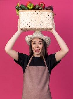 Sorpreso giardiniere femmina caucasica che indossa cappello da giardinaggio che tiene cesto di verdure sopra la testa isolato su parete rosa con spazio copia