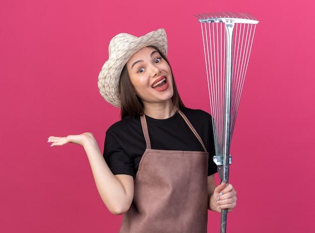 정원용 모자를 쓰고 놀란 백인 여성 정원사는 잎갈퀴를 들고 복사 공간이 있는 분홍색 벽에 손을 벌리고 있습니다
