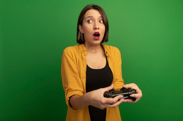 Surprised pretty caucasian woman holds game controller and looks at side isolated