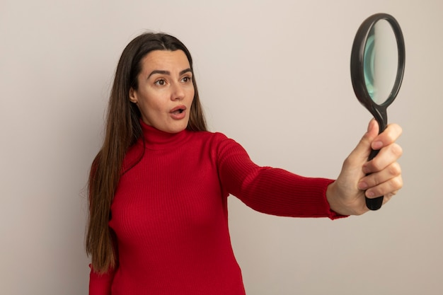 Surprised pretty caucasian woman holds and looks at magnifying glass on white