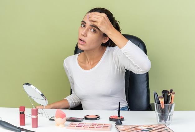 コピースペースのあるオリーブグリーンの壁に分離されたスポンジとトーンクリームを適用する化粧ツールでテーブルに座って驚いたかなり白人女性