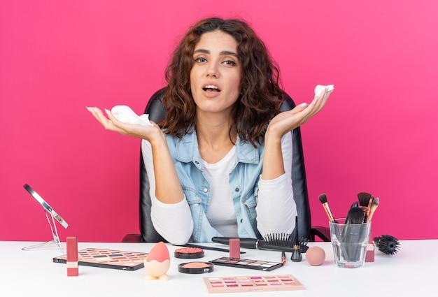 복사 공간이 있는 분홍색 벽에 격리된 헤어 무스를 들고 화장 도구를 들고 테이블에 앉아 놀란 예쁜 백인 여성