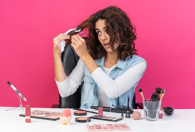 Surprised pretty caucasian woman sitting at table with makeup tools applying hair mousse